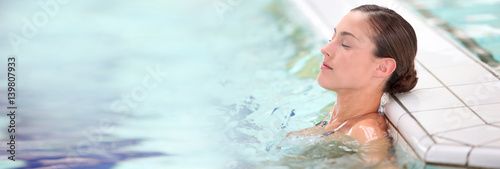 Vászonkép Beautiful young woman relaxing in seawater pool