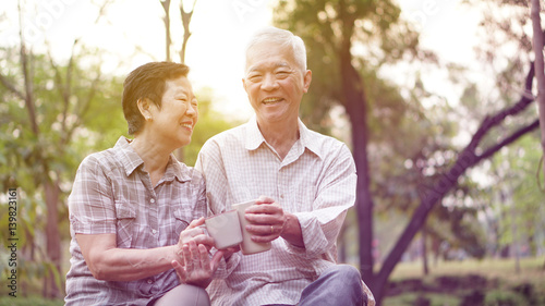 Fotografia  Healthy Asian senior couple drinking coffee in morning park together
