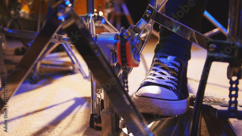 Drummer's foot in sneakers moving drum bass pedal Poster Mural XXL