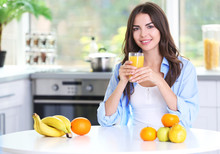 Beautiful Young Woman With Glass Of Orange Juice Sitting At Kitchen Table