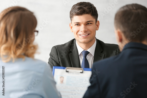 Valokuva  Human resources commission interviewing young man