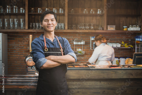 Obraz na plátne  Successful small business owner standing with crossed arms with employee in background preparing coffee