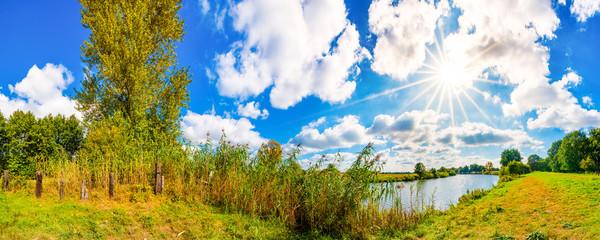 Landschaft im Sommer mit Sonne, Weide und Fluss