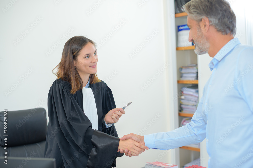 Fotografija  Female magistrate shaking hands with man