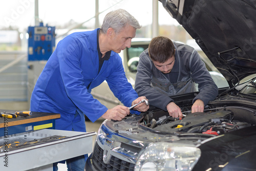 student with instructor repairing a car during apprenticeship Wallpaper Mural