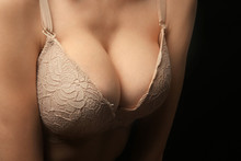 Young Woman In Beige Bra On Black Background