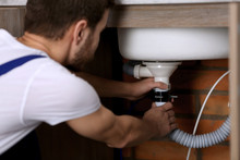 Handsome Young Plumber Repairing Sink Pipes In Kitchen