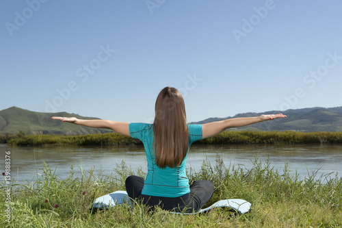 In de dag Ontspanning Young woman is practicing yoga at mountain river
