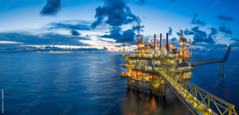 Fototapeta Panorama of Oil and Gas central processing platform in twilight, offshore hard work occupation twenty four working hours.