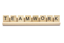 Word ''teamwork'' On Scrabble Wooden Letters On A Rack, Isolated On White Background. Lower Case Letters.