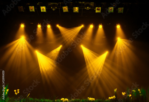 The yellow light from the spotlights through the smoke at the theater during the performance. Lighting equipment.