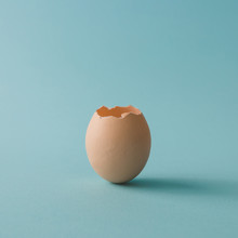 Egg Shell On Bright Blue Background. Minimal Concept.