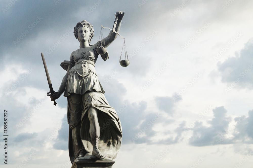 Fototapeta Justitia Symbol für Gerechtigkeit vor Himmel mit Wolken