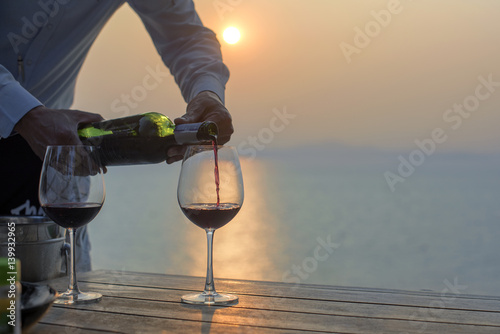 sommelier boy prepare pour wine into the glass at shadow light of sunset in background