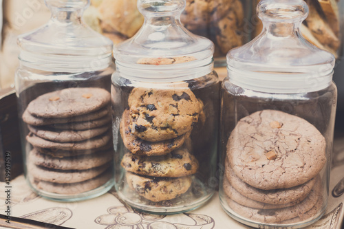 Photo Cookies and biscuits in glass jars on bar for sale