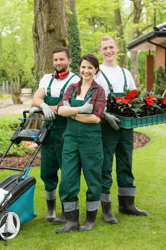 Happy gardeners with plants and lawn mower Plakát