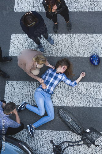Unconscious biker lying on the road after car crash - Buy this stock