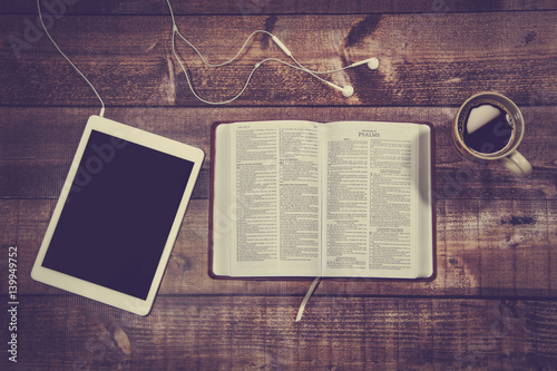 Fotografia  Bible with tablet and coffee in a wooded table