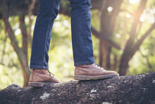 Close Ups Of Tourist Legs .Lonely Man Wearing Jeans And Brown Boots,he Standing On A Tree.