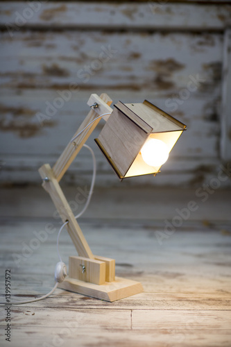 Photo  Homemade wooden table lamp on a background of cracked paint vintage wall