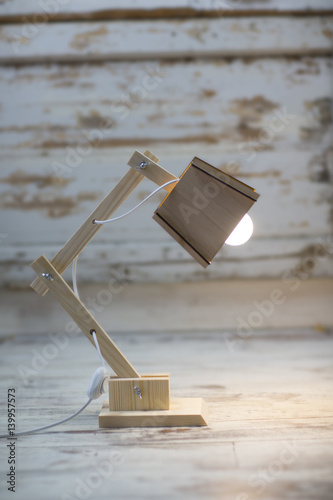 Photo  A homemade wooden table lamp shines on the floor against a cracked paint vintage