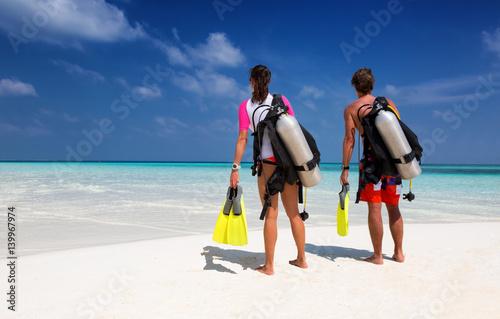 Tuinposter Duiken Taucher Paar am Strand schaut auf den Ozean