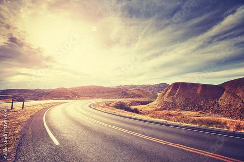 Poster Salmon Vintage toned scenic desert highway at sunset.