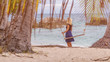 Girl standing behind the Swing on the Tropical Beach on Evening