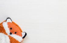 Fox Plush Cuddly Toy Orange On White Wooden Desk Background