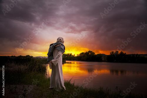 Jesus Christ overlooking a sun setting on the lake