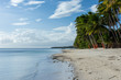 Palm tree lined white sand beach meets calm clear sea with clounds in the distance.