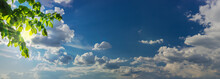 Sky Panorama With Sun Rays From Behind Branches And Clouds