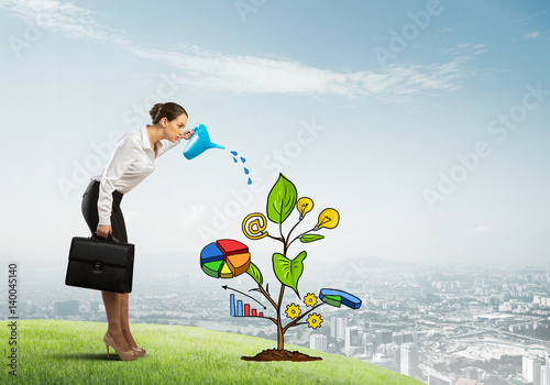 Fototapeta Young businesswoman outdoors watering drawn growth concept with can obraz