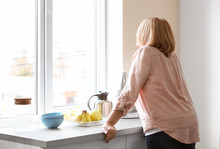 Depressed Senior Woman In Kitchen At Home