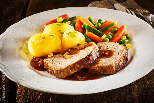 Photo  Sliced homemade roasted meat loaf with vegetables