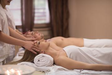 Obraz na płótnie Canvas couple enjoying head massage at the spa