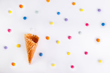 White Background With Colorful Candies And Empty Ice Cream Cone. Top View, Flat Lay. Selective Focus