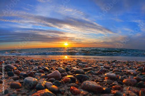 Fotomural  Beautiful sea sunset and sun glare on wet pebbles