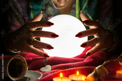 Hands of an female fortune teller around a crystal ball