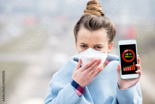 Fotografía Woman in protective mask holding smart phone with air polution measurement of PM