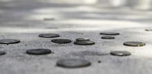 Coins At Eye Level On A Sidewalk