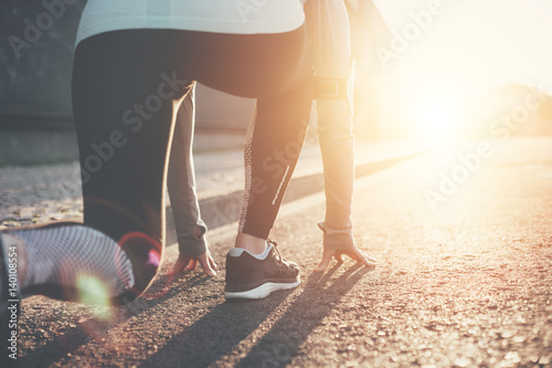 Athlete woman preparing for running on the city street. Sport tight clothes. Bright sunset, blurry background. Horizontal