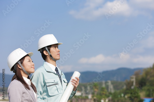 Engineers holding blueprint and looking up at construction site
