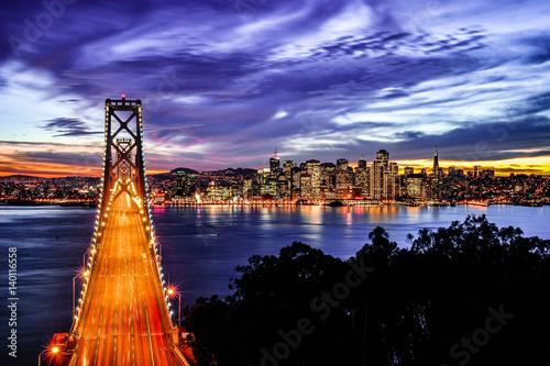 Fényképezés  Aerial View of San Francisco-Oakland Bay Bridge and San Francisco Skyline at sun