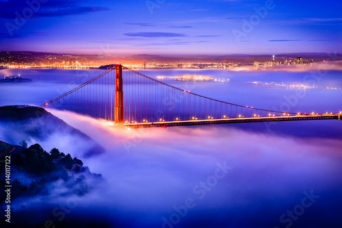 Vászonkép  Golden Gate Bridge at dawn surrounded by fog from Marin Headlands in San Francis