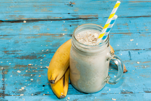 Poster Milkshake Smoothies with yogurt, banana and oatmeal in bowl. On rustic blue wooden table, with ingredients for cooking. Copy space