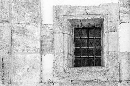 Fotografie, Obraz  Ventana con reja en pared de piedra