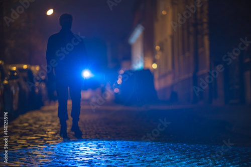 Obraz The man with a flashlight inspect the road. Evening night time - fototapety do salonu