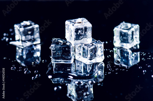 Iced cubes melting on a black table with reflection. Water. Melting of ice.