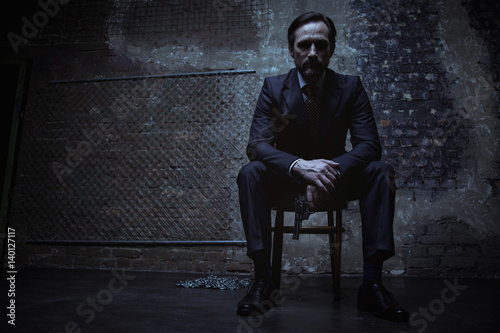 Fototapeta  Charming villain sitting in dark room